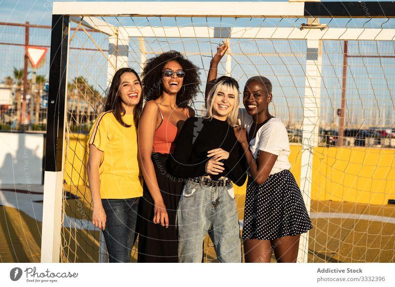 Fokussierte junge multirassische Freundinnen verbringen ihre Freizeit gemeinsam im Stadion aufwenden Frau Zusammensein Fußballtor Schüler genießen Zeitvertreib