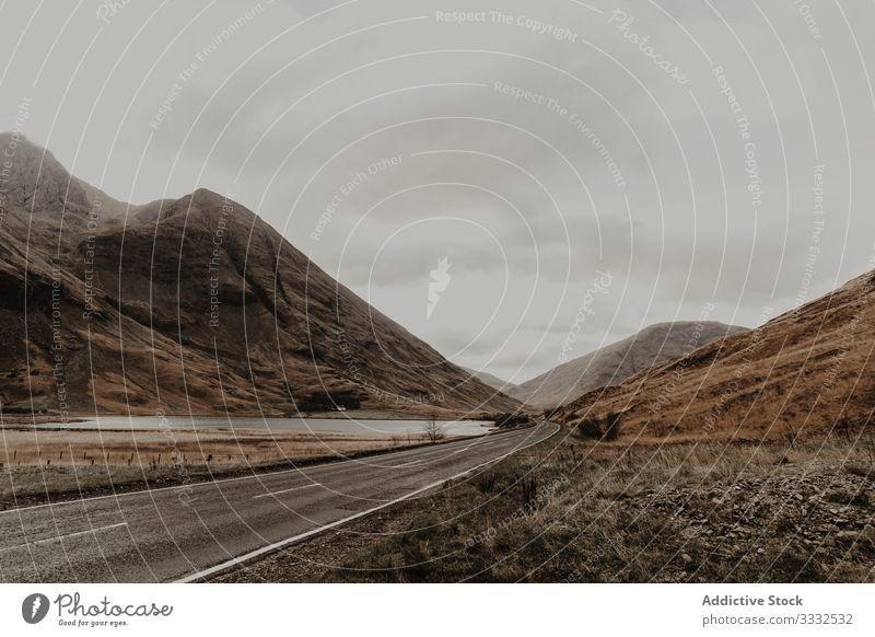 Leere Straße entlang eines Flusses, der von einem Berg umgeben ist Berge u. Gebirge Tal Hügel reisen Natur Landschaft Himmel Tourismus Abenteuer grau gefährlich