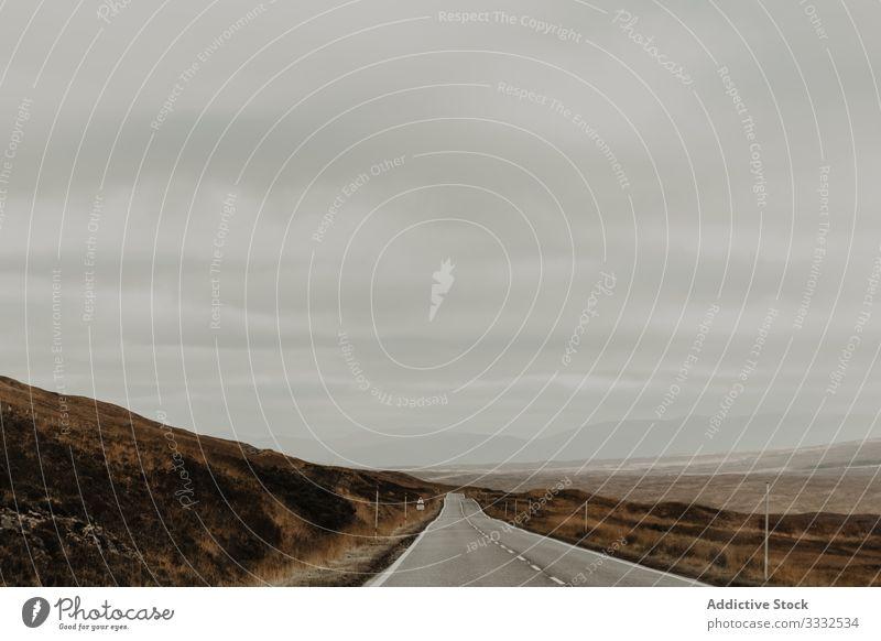 Leere Straße entlang eines trockenen Hügeltals bei grauem Tag Tal Berge u. Gebirge reisen Natur trocknen Landschaft Himmel Tourismus Abenteuer gefährlich extrem