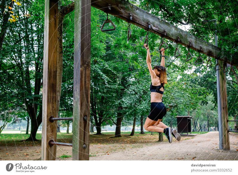 Frau macht Affenübungen auf Ringen Lifestyle Körper Sport Mensch Erwachsene Baum Park Wege & Pfade Turnschuh Fitness dünn stark Kraft anstrengen Sportlerin