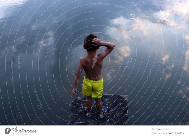 Kind schaut von einem Felsenvorsprung auf ein Gewässer in dem sich der Himmel spiegelt träumen Selbstvertrauen Wasser Wolken Spiegelung Reflexion & Spiegelung