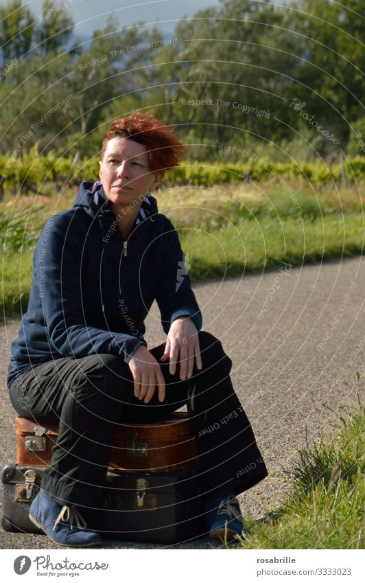 bestellt und nicht abgeholt | wörtlich genommen | - Frau mittleren Alters sitzt abwartend auf gepackten Koffern auf einer schmalen Landstraße im Grünen bei Wind