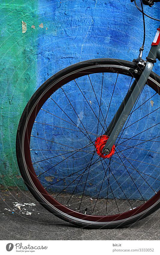 Vorderrad mit Speichen vom Rad, steht geparkt, angelehnt vor blauer, knalliger Wand, bei Pause der Fahhradtour, in der Stadt. Freizeit & Hobby Sport Fitness