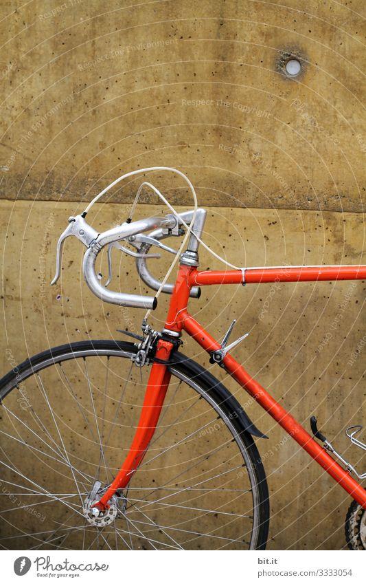 Orangenes Rennrad von einem sportlichen Hipster, steht während einer Pause, geparkt vor einer braunen Wand, im Ausschnitt sind Lenker, Reifen, Vorderrad, Bremse und Gestell des Rades im alten, Retrostil zu sehen.