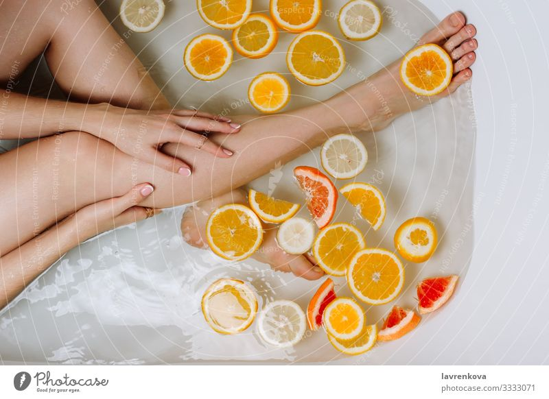Hand und Beine der Frau in einer mit Wasser gefüllten Badewanne aromatisch Schwimmen & Baden Beautyfotografie Bombe Blase Schaumblase Pflege Zitrone
