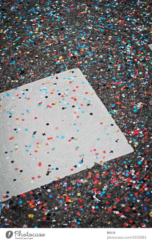Viel, buntes Konfetti liegt verteilt bei Fasnacht, Karneval, Fasching, Fest, Feier auf dem grauen Boden der Straße mit Markierung und sorgt für Müll und Schmutz.