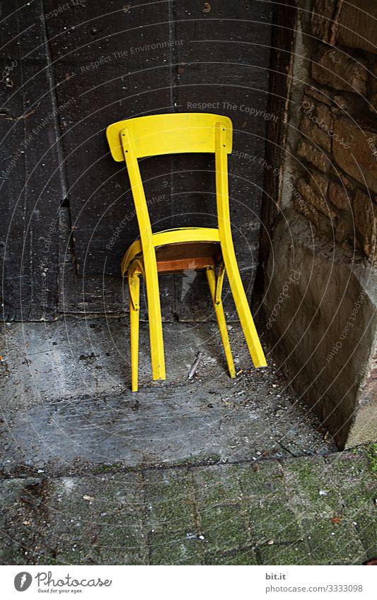 Knallig, gelber, alter, unbenutzter Holzstuhl, steht angelehnt, gekippt, an einer alten Tür aus Holz in einem alten, verlassenen Eingang von einem Haus / Scheune aus Stein.