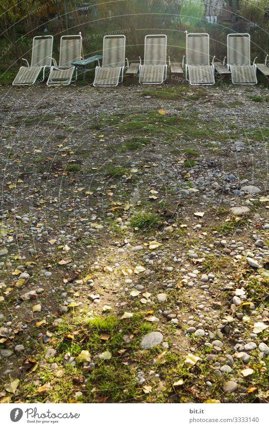 Alte, kaputte, ungepflegte, weisse, leere Liegestühle aus Plastik, stehen nebeneinander in einer Reihe, im Licht auf einem Liegeplatz mit Gras und Steinen und warten auf Urlauber / Besucher.