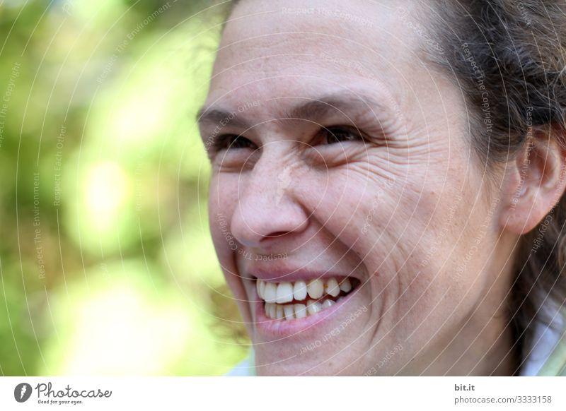 Junge, natürliche, symphatische, authentische Frau schaut nach oben und lacht herzhaft. Fröhliche Frau mit Lachfältchen draussen in der Natur vor grün-gelben, leuchtendem Bokeh. Optimistische, neugierige, fröhliche, feminine Person schaut lachend hoch.