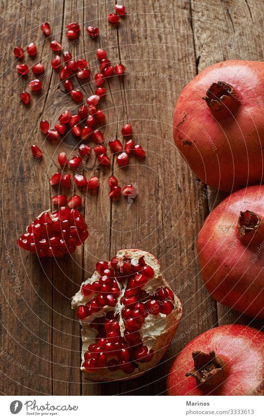 reife Granatapfelfrüchte auf Holztisch. Frucht Dessert Vegetarische Ernährung Diät Saft Garten Tisch frisch natürlich saftig rot Farbe Gesundheit Vitamin