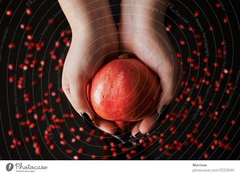 Hände, die einen Granatapfel halten. Frucht Dessert Vegetarische Ernährung Diät Saft Garten frisch natürlich saftig rot schwarz Farbe Gesundheit Vitamin