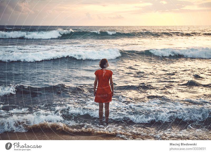 Frau in orangem Kleid steht bei Sonnenuntergang im rauen Meer still Lifestyle Erholung Freizeit & Hobby Ferien & Urlaub & Reisen Tourismus Ausflug Abenteuer