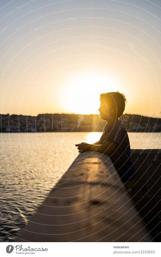 Ein süßes Kind, das einen erstaunlichen Sonnenuntergang in Argostoli, Griechenland, erlebt. Lifestyle Freude Glück schön Gesicht Freizeit & Hobby