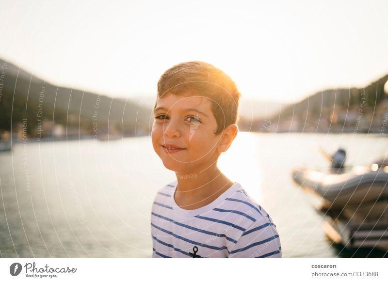 Süßes Kind lächelt bei Sonnenuntergang mit dem Meer im Hintergrund Lifestyle Freude Glück schön Gesicht Ferien & Urlaub & Reisen Tourismus Freiheit Sommer