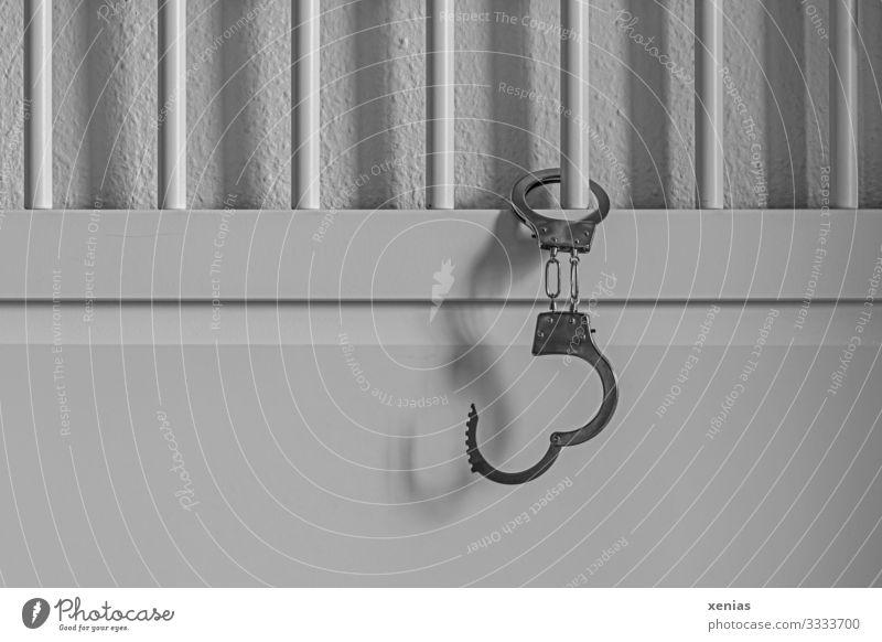 Handschellen hängen am weißen Bett mit Gitterstäben Sextourismus Wohnung Schlafzimmer Hotelzimmer Spielzeug Erotik silber Begierde Angst Hemmungslosigkeit