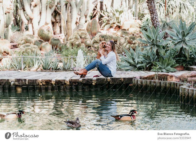 junge Frau und ihr süßer Cockerspaniel-Welpe im Freien in einem Park mit einem See Hund Haustier Sonnenstrahlen Außenaufnahme Liebe Umarmen Lächeln Rückansicht