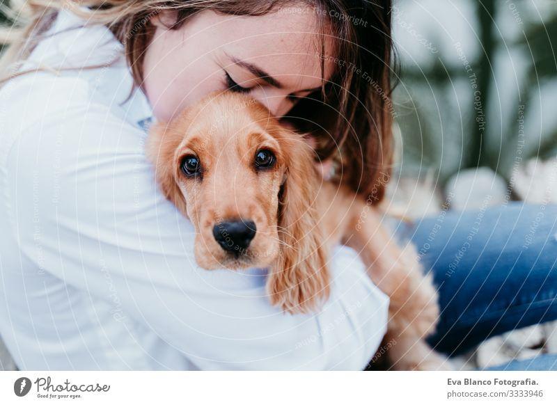 junge Frau und ihr niedlicher Cockerspaniel-Welpe im Freien Hund Haustier Park Sonnenstrahlen Außenaufnahme Liebe Umarmen Lächeln Rückansicht Küssen züchten