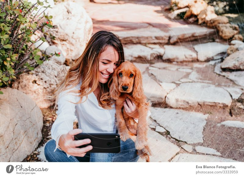 junge Frau, die mit ihrem süßen Cockerspaniel-Welpen einen Selfie mit nach draußen nimmt Handy Technik & Technologie Cocker Spaniel Hund Haustier Park