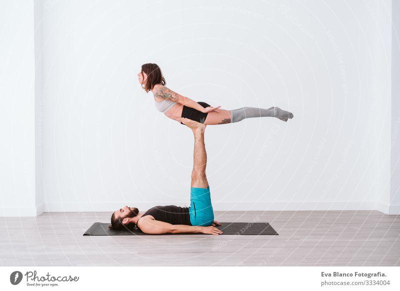 junges Paar, das in einem weißen Studio oder einer Sporthalle Akro-Yoga praktiziert. Gesunder Lebensstil im Innenbereich Gesundheit Mann Kraft Mensch