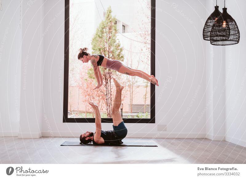 junges Paar, das Akro-Yoga am Fenster im Studio oder im Fitnessstudio praktiziert. Gesunder Lebensstil Sport Sporthalle Gesundheit Mann Kraft Mensch