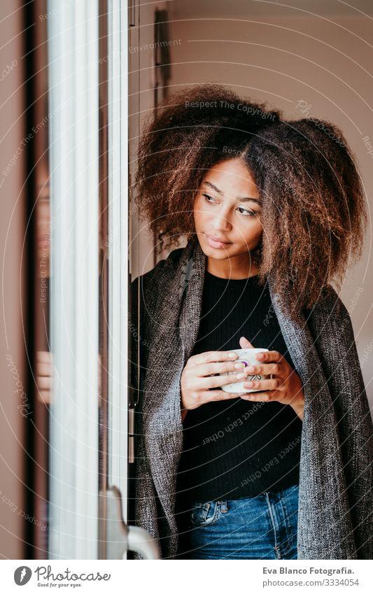 Porträt einer schönen afroamerikanischen jungen Frau am Fenster mit einer Tasse Kaffee. Lebensstil im Haus Afroamerikaner heimwärts urwüchsig