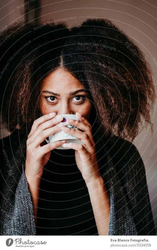 Porträt einer schönen afroamerikanischen jungen Frau am Fenster, die Tee oder Kaffee trinkt. Lebensstil im Haus Afroamerikaner heimwärts urwüchsig