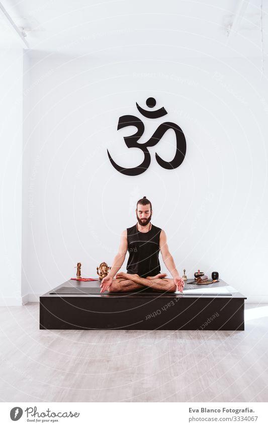 junger Mann, der im Fitnessstudio Yoga-Sport betreibt. Gesunder Lebensstil Junge Gesundheit Lifestyle Innenaufnahme