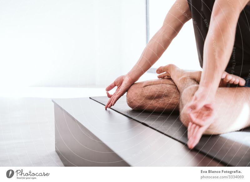 junger Mann, der im Fitnessstudio Yoga-Sport betreibt. Gesunder Lebensstil. Nahaufnahme Junge Gesundheit Lifestyle Innenaufnahme
