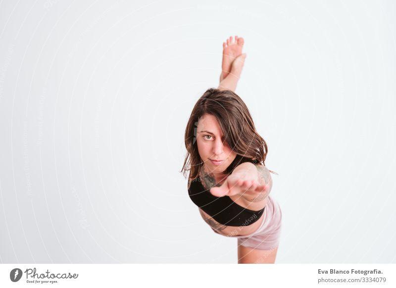 junge tätowierte Frau, die im Fitnessstudio Yoga-Sport betreibt. Gesunder Lebensstil Jugendliche Gesundheit Lifestyle