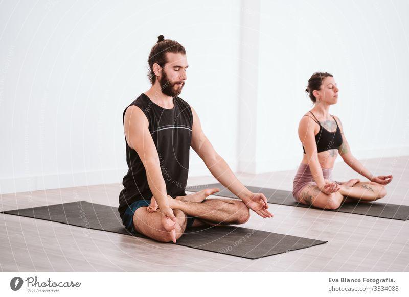 junger Mann und Frau, die in der Sporthalle Yoga-Sport betreiben. Gesunder Lebensstil Junge Gesundheit Lifestyle Innenaufnahme