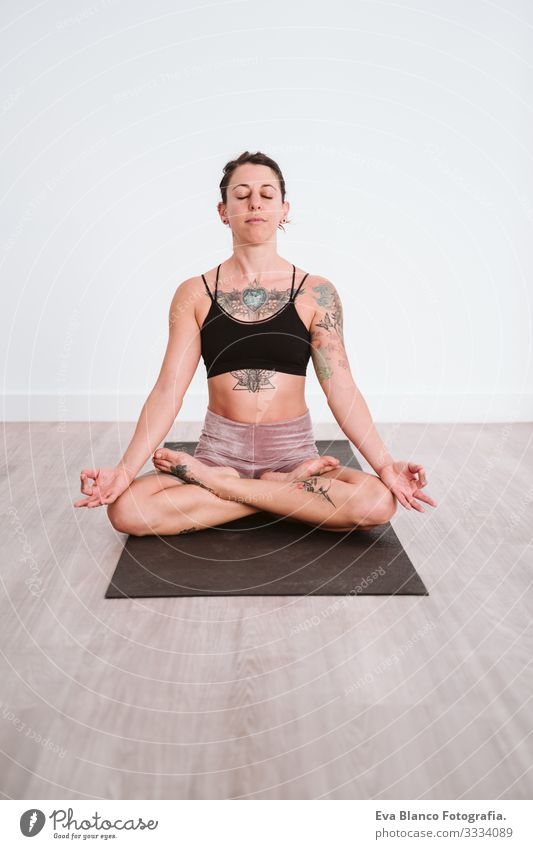 junge tätowierte Frau, die im Fitnessstudio Yoga-Sport betreibt. Gesunder Lebensstil Mann Junge Gesundheit Lifestyle Innenaufnahme