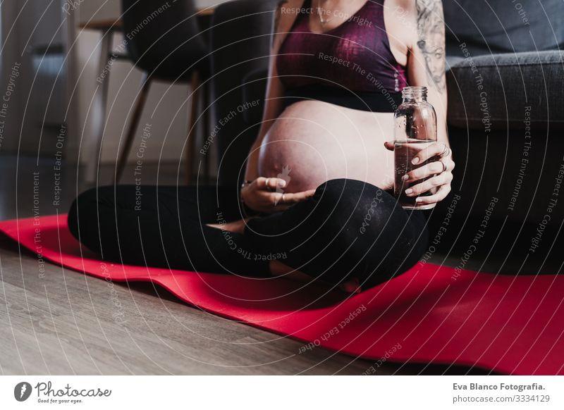 junge schwangere Frau, die zu Hause Yoga-Sport und Trinkwasser praktiziert, gesunde Lebensweise heimwärts Gesundheit Lifestyle Jugendliche