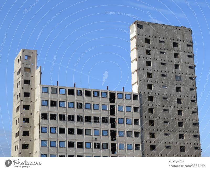 leerstehendes Bürogebäude kurz vor dem Abriss Abrissgebäude Hochhaus Beton hoch grau blau Himmel schwarz Ruine Bauruine entkernt fensteröffnung Gebäude schmal