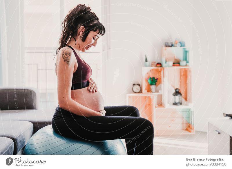 junge schwangere Frau zu Hause auf Pilates-Ball sitzend, gesunde Lebensweise Yoga heimwärts Sport Gesundheit Lifestyle Jugendliche