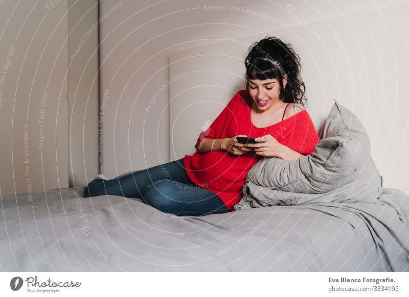 junge schwangere Frau zu Hause, die ein Mobiltelefon benutzt Handy Technik & Technologie heimwärts Bett PDA Baby