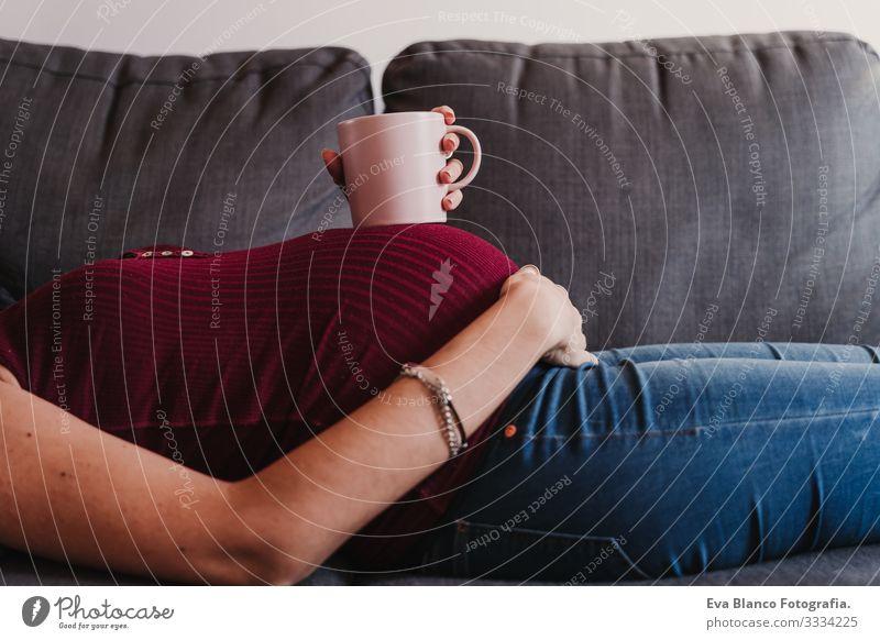 Porträt einer jungen schwangeren Frau zu Hause, die auf dem Sofa liegt und eine Tasse auf dem Bauch hält heimwärts Lifestyle Fenster Tag Leben