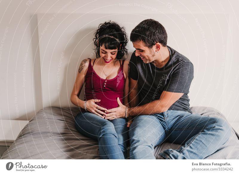 junges Paar zu Hause, das sich umarmt. Glückliche schwangere Frau lächelt Liebe Eltern heimwärts Sofa Umarmen