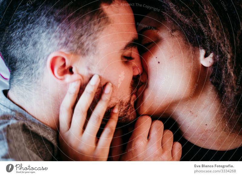 Glückliches, verliebtes Paar zu Hause. Afroamerikanische Frau und kaukasischer Mann. ethnisches Liebeskonzept Afroamerikaner urwüchsig heimwärts Bett
