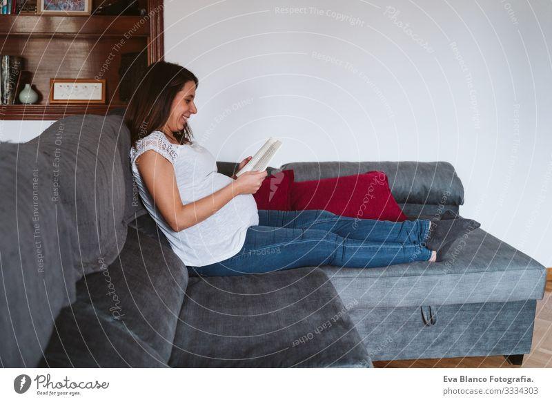 junge schwangere Frau zu Hause, die ein Buch liest Jugendliche lesen heimwärts Leben Lounge