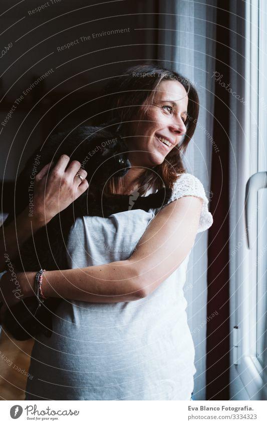 junge schwangere Frau zu Hause, die eine schwarze Katze auf der Schulter hält Jugendliche heimwärts Leben bauchfrei Erholung