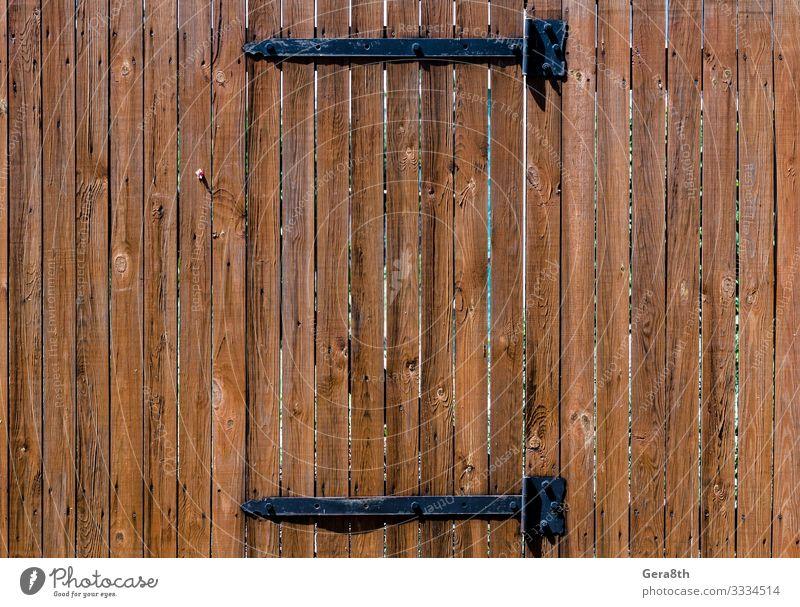 Textur Holzzaun mit einer Holztür auf Eisenscharnieren braun Knüppel Tür Zaun natürlicher Baum Konsistenz Bretterzaun Farbfoto Außenaufnahme Muster Tag