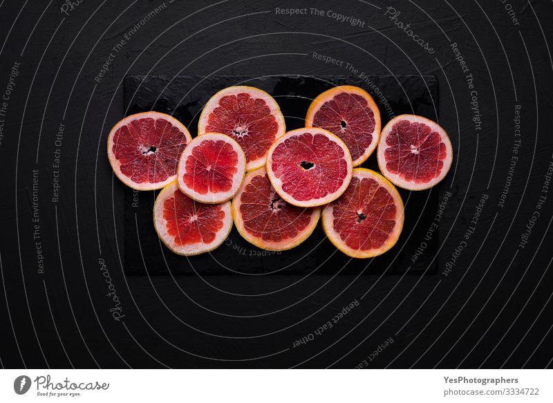 Grapefruitscheiben auf einem schwarzen Tisch. Geschnittene frische Zitrusfrüchte Lebensmittel Frucht Frühstück Gesunde Ernährung Gesundheit obere Ansicht