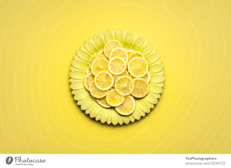 Zitronenscheiben auf gelber blütenförmiger Platte. Zitrusfrüchte in Scheiben Lebensmittel Frucht Frühstück Teller Gesunde Ernährung hell obere Ansicht ganz gelb