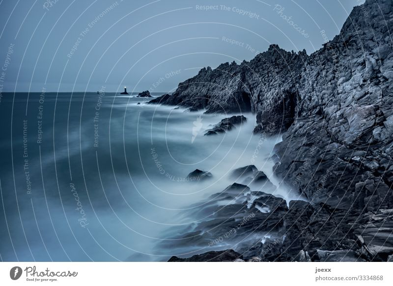 Leuchtturm vor Felsküste und Meer Weitwinkel Außenaufnahme Farbfoto Horizont Hoffnung Fernweh ruhig weiß blau maritim Küste Wellen Felsen Wolken Himmel Wasser