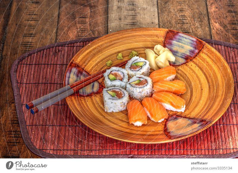 Lachs-Sushi-Rollen und Sake mit Wasabi Lebensmittel Fisch Mittagessen Teller Gesunde Ernährung orange Reiswein roher Fisch Mahlzeit Rohkost Essstäbchen Ingwer