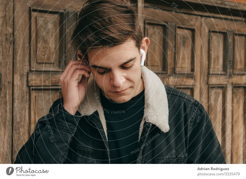 Männlicher Teenager, der mit drahtlosen Kopfhörern Musik hört Freiheit Winter Entertainment Telefon Headset Technik & Technologie Mann Erwachsene hören modern