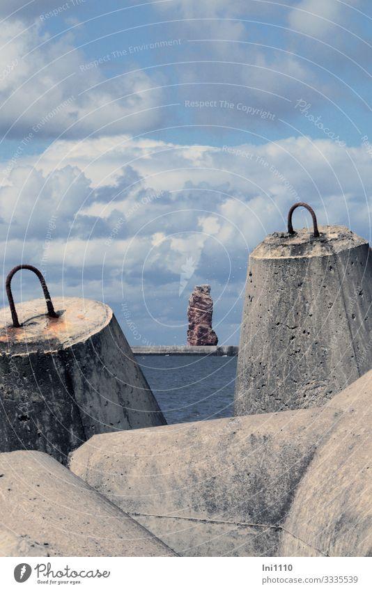 Blick durch zwei Tetrapoden übers Meer auf Lange Anna auf Helgoland vor blauem Wolkenhimmel Fortschritt Zukunft Natur Landschaft Küste Nordsee Insel grau rot
