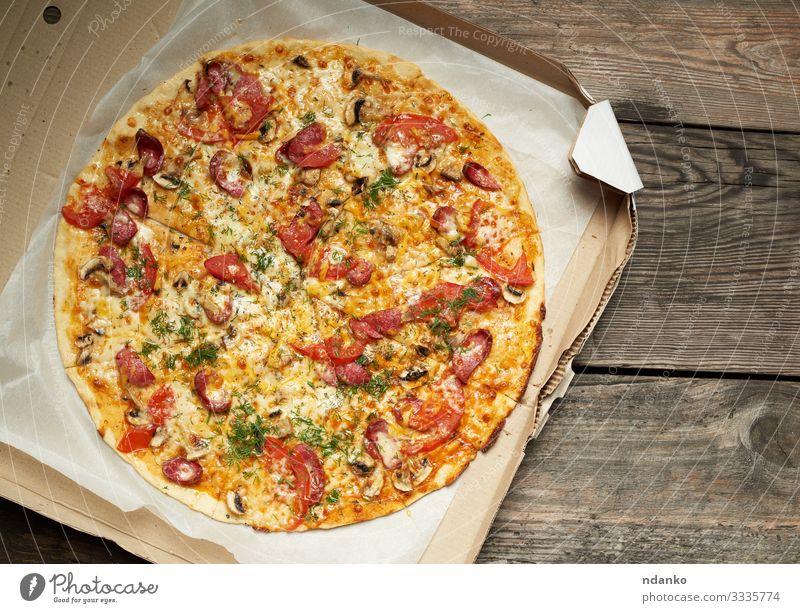 gebackene runde Pizza mit geräucherten Würsten Fleisch Wurstwaren Käse Gemüse Teigwaren Backwaren Mittagessen Abendessen Fastfood Tisch Restaurant Verpackung
