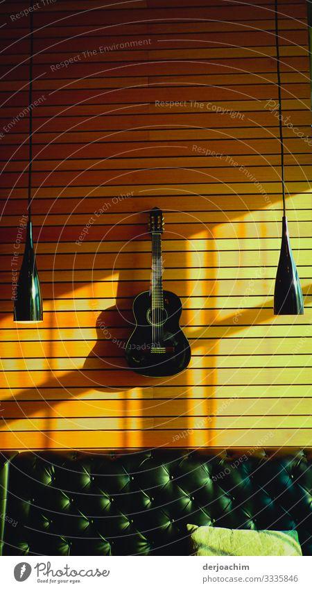 Gitarre an der Holzwand. Mit Rechts und links zwei hängende Lampen  und unten ein Leder Sofa mit Kissen. Freude Erholung Ausflug Raum Umwelt Schönes Wetter