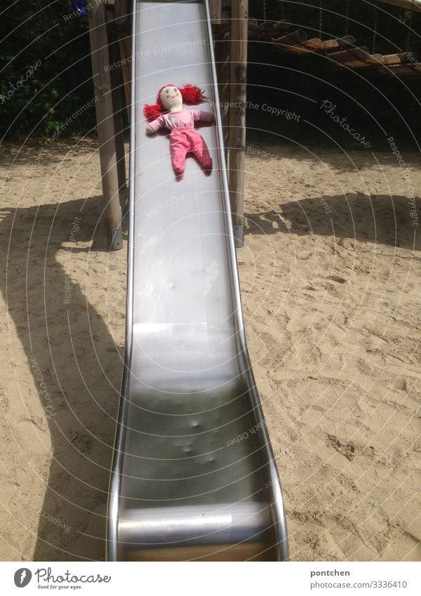 Weibliche rothaarige Puppe liegt auf einer Rutsche am Spielplatz Freizeit & Hobby Spielen Sommer puppenkleidung feminin Schatten vergessen verloren Entführung